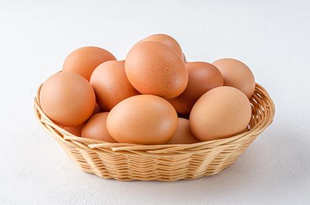 Red chicken eggs in a basket.